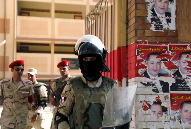 Security forces stand guard outside a school used as a polling station in Alexandria, Egypt, October 18, 2015. Egypt's long-awaited parliamentary election got off to a slow start on Sunday, marking the final step in a process that was meant to restore democracy but which critics say has been undermined by state repression. (Photo by Asmaa Waguih/Reuters)