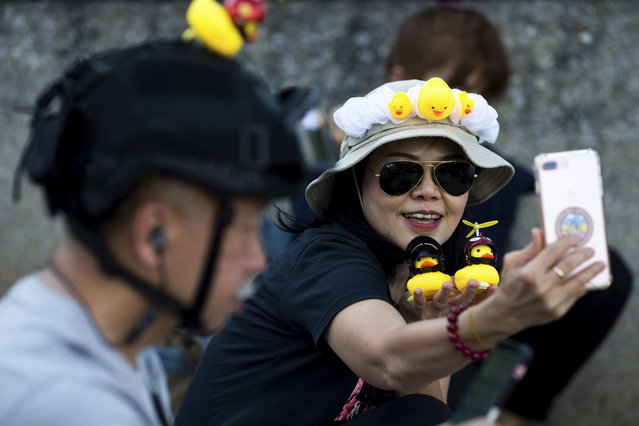 A protester takes a selfie with yellow ducks, which have become good-humored symbols of resistance during anti-government rallies, on Wednesday, November 25, 2020, in Bangkok Thailand. (Photo by Wason Wanichakorn/AP Photo)