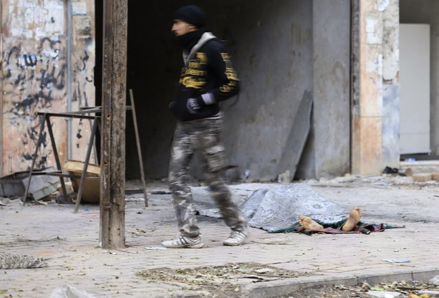 A man walks past a dead body, whom according to rebel fighters, is a soldier loyal to Syria's President Bashar al-Assad, in Jobar, a suburb of Damascus December 22, 2014. Rebel fighters said the body was pulled from the frontline after an offensive by forces loyal to Syria's President Bashar al-Assad in an attempt to advance in the area but failed to do so. (Photo by Bassam Khabieh/Reuters)