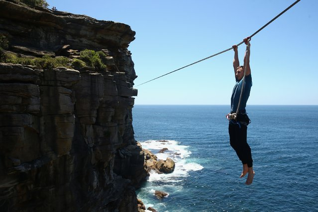 Antek Marciniec holds onto a slackline after falling off as he highlines between two cliffs at Diamond Bay on December 21, 2014 in Sydney, Australia. Slacklining is a balance sport in which participants walk on a flat nylon webbing anchored between two points with the tension adjusted to allow for slack, providing an experience similiar to that of walking on a trapmoline. Highlining is a style of slacklining where the two anchor points are set up with significant elevation from the ground or water. (Photo by Cameron Spencer/Getty Images)