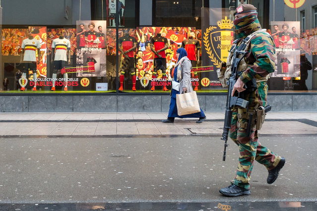 A Belgian Army soldier patrols in a shopping street in the center of Brussels on Wednesday, November 25, 2015. Students in Brussels have begun returning to class after a two-day shutdown over fears that a series of simultaneous attacks could be launched around the Belgian capital. Underground transport in Brussels is also slowly starting up again after a four-day closure. (Photo by Geert Vanden Wijngaert/AP Photo)