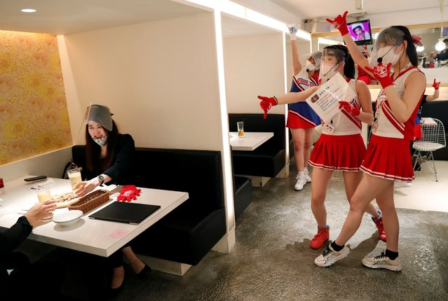 "Waitresses wearing protective masks, face-shields and gloves to prevent infections following the coronavirus disease (COVID-19) outbreak, gesture to customers toasting glasses at the cheerleader-themed restaurant ""Cheers One"" in Tokyo, Japan on May 11, 2020. (Photo by Kim Kyung-Hoon/Reuters)"