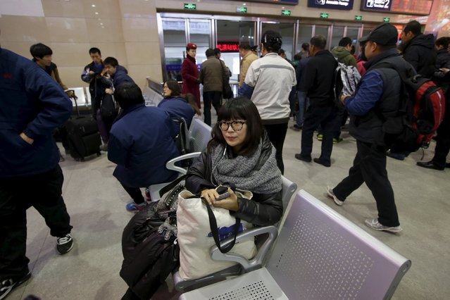 Li Nan, a makeup artist, waits at a train station on her commute into Beijing for work from Tianjin, China, November 18, 2015. (Photo by Jason Lee/Reuters)
