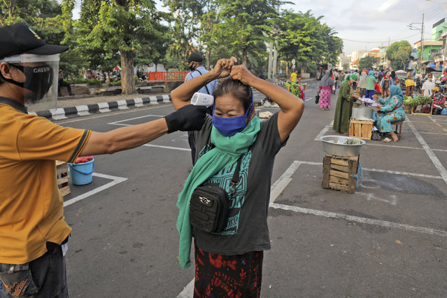 A city official takes the temperature reading of a vendor as others sit on a marked positions to maintain physical distancing in an attempt to curb the spread of the new coronavirus outbreak at a traditional market in Surabaya, East Java, Indonesia, Wednesday, June 3, 2020. (Photo by Trisnadi/AP Photo)