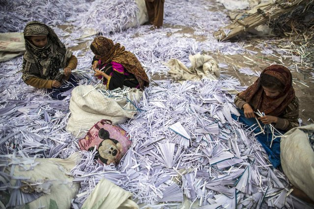 Razia (R), 9, Amna (C), 11 and Saadia, 10 sort papers before they are taken to a factory to be recycled in Lahore January 12, 2015. (Photo by Zohra Bensemra/Reuters)