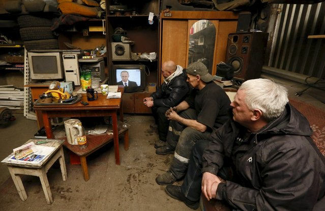 Workers watch a television broadcast of Russian President Vladimir Putin address to the Federal Assembly at an auto repair shop in the Siberian town of Divnogorsk near Krasnoyarsk, Russia, December 3, 2015. Putin used his annual state of the nation speech on Thursday to warn Turkey the Kremlin planned to adopt further sanctions against it to punish Ankara for shooting down a Russian warplane near the Syrian-Turkish border last week. (Photo by Ilya Naymushin/Reuters)