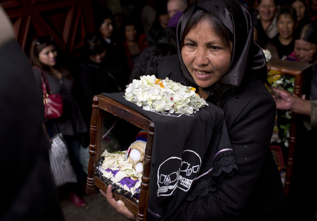"""A woman carries a decorated human skull or """"natitas"""", after a blessing by the priest inside the Cementerio General chapel, during the Natitas Festival celebrations, in La Paz, Bolivia, Tuesday, November 8, 2016. The """"natitas"""" are cared for and decorated by faithful who use them as amulets believing they serve as protection, the tradition marks the end of the Catholic All Saints holiday, but is not recognized by the Catholic church. (Photo by Juan Karita/AP Photo)"""