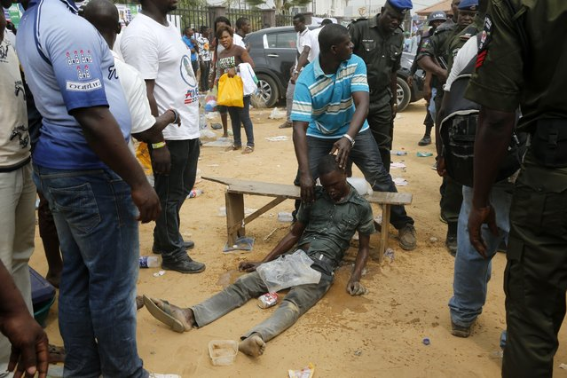A man helps a gangster who passed out after a fight between rival gangs at a campaign rally for the governorship candidate of All Progressives Congress (APC) Akinwunmi Ambode in Oworonshoki district in Lagos January 19, 2015. As Nigeria approaches its most divisive and closely fought election since the end of military rule in 1999, its leaders are having to reassure voters that Africa's most populous nation will remain in one piece. (Photo by Akintunde Akinleye/Reuters)