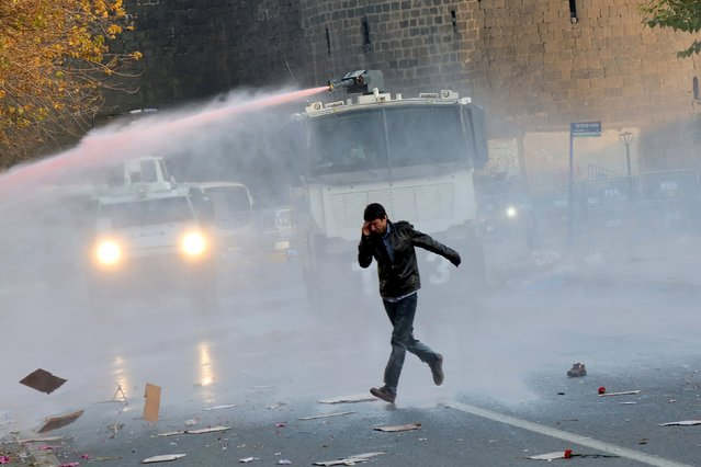 Riot police use water cannon to disperse demonstrators during a protest against the curfew in Sur district in the Kurdish dominated southeastern city of Diyarbakir, Turkey, December 10, 2015. Seven Kurdish militants and a policeman have been killed in four days of fighting in a southeastern Turkish province that has been under curfew all week, security sources said. Nusaybin, a district of Turkey's southeastern province of Mardin on the Syrian border, has been under curfew since Sunday. (Photo by Sertac Kayar/Reuters)