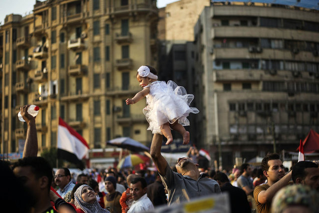 """An Egyptian man carries his daughter in Egypt's landmark Tahrir square on July 4, 2013. Egypt's Muslim Brotherhood, from which ousted president Mohamed Morsi hails, denounced a new """"police state"""" after the arrest of Islamist leaders and the closure of satellite channels. (Photo by Gianluigi Guercia/AFP Photo)"""
