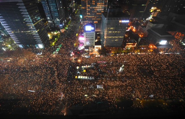 Protesters hold candles during an anti-government rally in central Seoul on November 12, 2016. (Photo by Jung Yeon-Je/AFP Photo)
