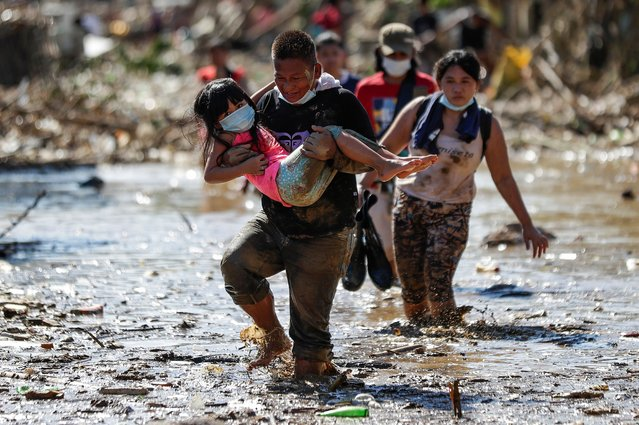 A man carries a girl through debris and floods in the typhoon-damaged Kasiglahan village in Rodriguez, Rizal province, Philippines on Friday, November 13, 2020. Thick mud and debris coated many villages around the Philippine capital Friday after Typhoon Vamco caused extensive flooding that sent residents fleeing to their roofs and killing dozens of people. (Photo by Aaron Favila/AP Photo)