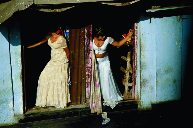 Prostitutes, who are known as cage girls and are often s*x slaves, display themselves on a Mumbai street in India, 2004. (Photo by Jodi Cobb/National Geographic)