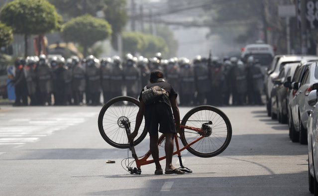 A demonstrator places his bicycle in front of riot police during a protest against the military coup, in Yangon, Myanmar, 27 February 2021. Anti-coup demonstrations continued despite intensifying use of force by security forces against protesters after weeks of unrest since the 01 February military coup. (Photo by Lynn Bo Bo/EPA/EFE)