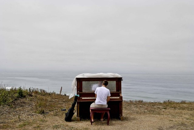 """Music student Dylan Gibbs, of Simsbury, Conn., plays a piano rested on a bluff at Poplar State Beach in Half Moon Bay., Calif., on July 15, 2013. Twelve  pianos were strategically placed along various locations along the San Mateo County coastline as part of an art project entitled """"Opus Two for Twelve Pianos"""" by area artist Mauro Ffortissimo. The artist and supporters have also been staging sunset piano recitals along the coast and inviting visitors to play the pianos. (Photo by Marcio Jose Sanchez/Associated Press)"""