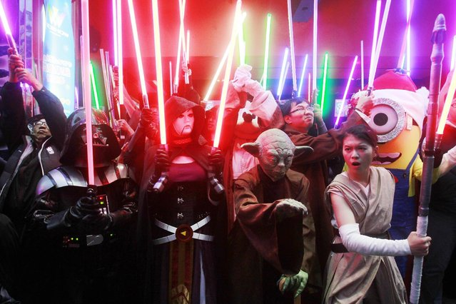 "Fans dressed as Star Wars characters parade outside a movie theater showing ""Star Wars: The Force Awakens"" Saturday, December 19, 2015, in Taipei, Taiwan. (Photo by Chiang Ying-ying/AP Photo)"