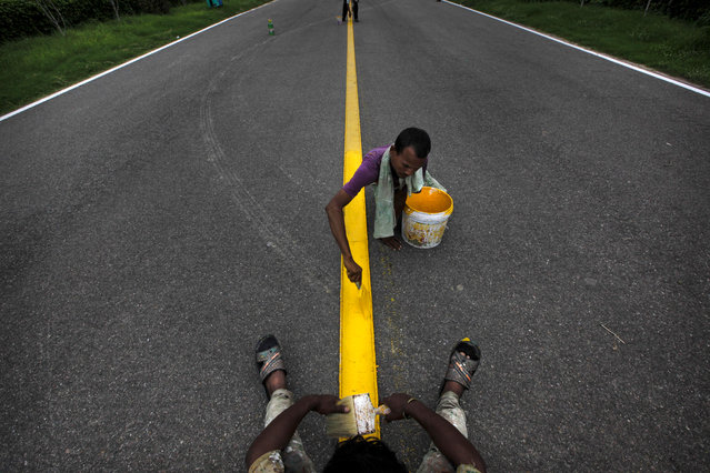 Indian laborers paint the center yellow line at the ceremonial boulevard Rajpath ahead of Independence Day celebrations in New Delhi, India, Wednesday July 31, 2013. India celebrates Independence Day on August 15. (Photo by Manish Swarup/AP Photo)