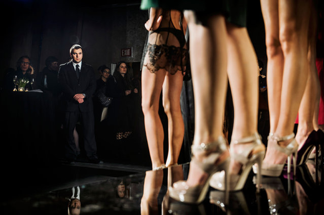 "A security guard looks at the models during La Perla's presentation at the Dream Hotel. Mercedes-Benz Fashion Week, New York City, Spring 2014. From the series ""Fashion Lust"". (Photo by Dina Litovsky)"