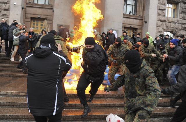 Ukrainian protesters burn tires outside the city council building as they protest against raising the public transport rates  in Kiev, Ukraine, Monday, February 9, 2015. Public transport rates have doubled since last weekend. (Photo by Oleg Batrak/AP Photo)