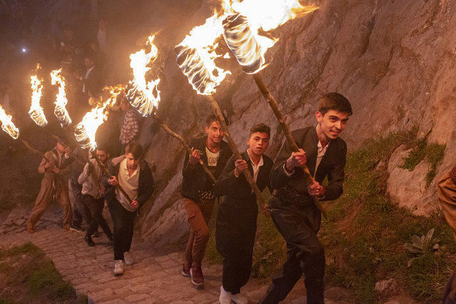Iraqi Kurds carry lit torches up Kali mountain to celebrate Nowruz, the Persian new year, on March 20, 2021 in Akre, Iraq. The Persian New Year is an ancient Zoroastrian tradition celebrated by Iranians and Kurds which coincides with the vernal (spring) equinox and is calculated by the solar calendar. (Photo by Sam Tarling/Getty Images)