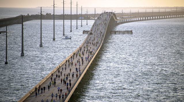 This handout photo released by the Florida Keys News Bureau shows an aerial photo of 1,000 registered competitors heading to the highest point of the Seven Mile Bridge in the Florida Keys during the Seven Mile Bridge Run on April 17, 2021, near Marathon, Florida. The annual contest was canceled in 2020 because of Covid-19 and this year's field was only comprised of runners who had registered in 2020. The race began in 1982 to mark the completion of a new Seven Mile Bridge as well as construction of 36 other spans to replace aging bridges that once carried the Florida Keys Oversea Railroad. (Photo by Andy Newman/Florida Keys News Bureau/AFP Photo)