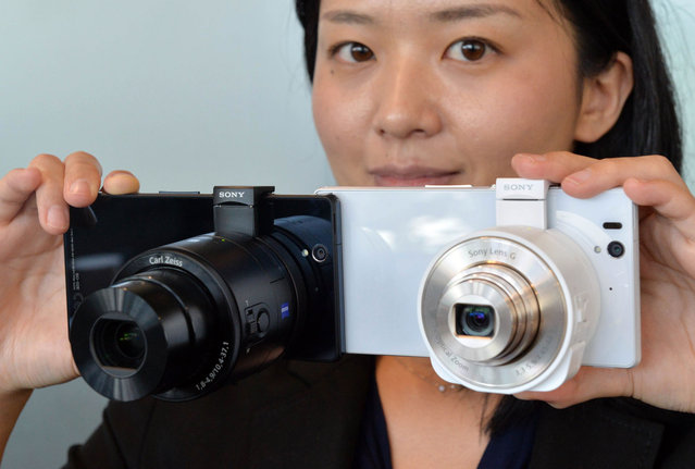 """A Japan's electronics giant Sony employee displays the new concept digital camera """"Cyber-shot DSC-QX100"""" (L) and """"Cyber-shot DSC-QX10"""", called lens-style cameras, which can turn a smartphone into a full digital camera, at the company's headquarters in Tokyo on September 12, 2013. The DSC-QX100, equipped with a 20 mega-pixel image sensor, can be operated from the smartphone with Wi-Fi connection, and will hit the market on October 25. (Photo by Yoshikazu Tsuno/AFP Photo)"""