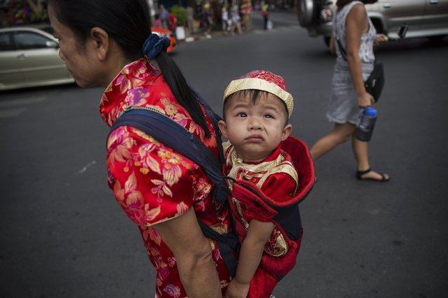 A woman carries her child, both wearing traditional red clothes celebrating the Chinese Lunar New Year in Bangkok February 19, 2015. (Photo by Damir Sagolj/Reuters)