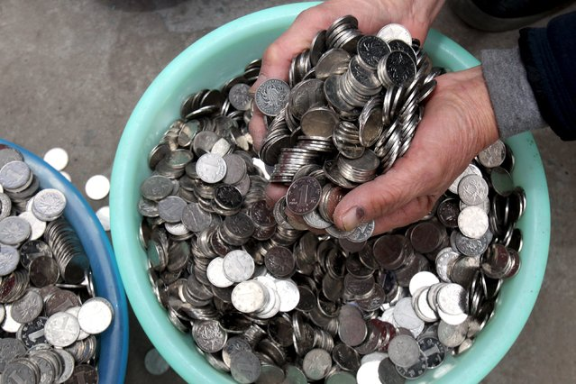 A man scoops a handful of one-yuan coins collected from coin-operated laundry machines, as he shows them to reporters in Zhengzhou, Henan province, China, January 11, 2016. (Photo by Reuters/Stringer)