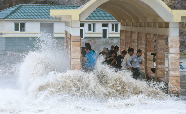 People dodge as a storm surge hits the coastline under the influence of Typhoon Fitow in Wenling, Zhejiang province, October 6, 2013. China issued a red alert ahead of Typhoon Fitow, which landed at east of the country on early Monday, according to local media. (Photo by Reuters/China Daily)