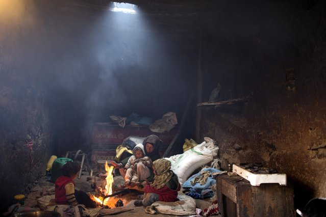 A woman and her children warm themselves around a fire in their home in Tilmi village in the High Atlas region of Morocco February 13, 2015. (Photo by Youssef Boudlal/Reuters)