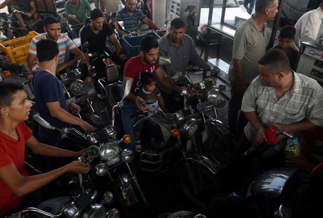 Palestinians wait to fill their motorcycle with fuel after Israel stopped the transfer of fuel and cooking gas into Gaza, at a petrol station in Khan Younis in the southern Gaza Strip July 17, 2018. (Photo by Ibraheem Abu Mustafa/Reuters)