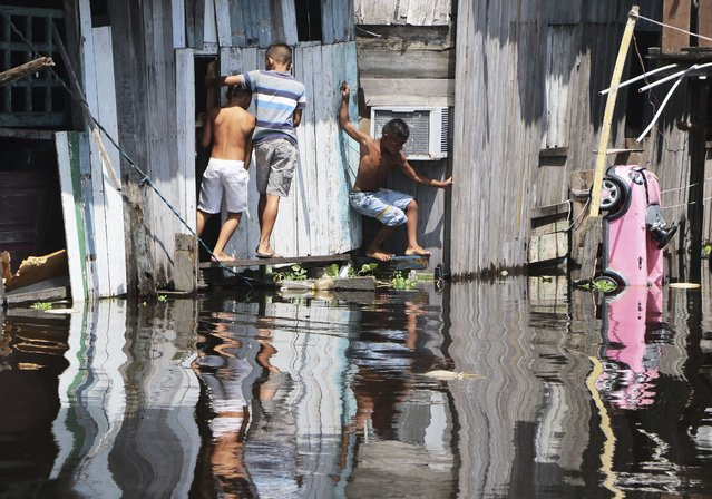 Children play outside a house, surrounded by the floodwaters of the Negro River in Manaus, Brazil, Thursday, May 20, 2021. According to official records taken by the Port of Manaus, the city is facing one of its worse floods in years, with levels not seen since 1902, making it the second-worst flood ever recorded. (Photo by Edmar Barros/AP Photo)