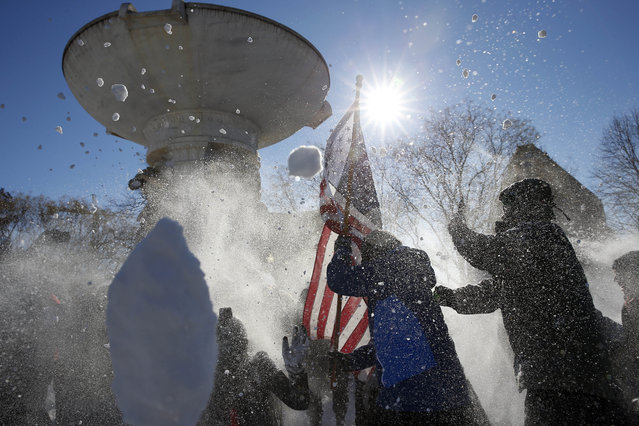A person holds an American Flag during a charge during an organized snowball fight at Dupont Circle Sunday, January 24, 2016 in Washington. (Photo by Alex Brandon/AP Photo)