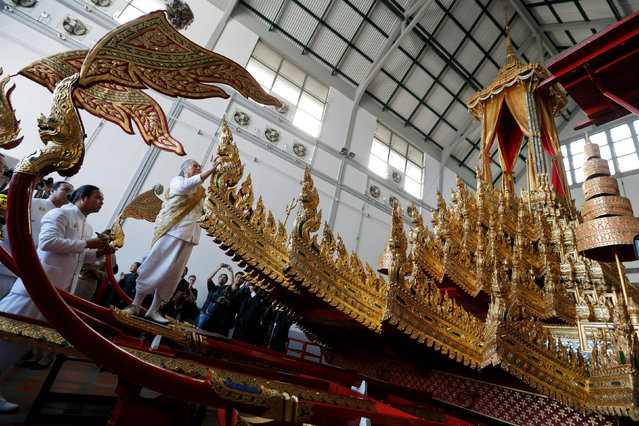 A Brahmin conducts a ceremony to mark the beginning of the restoration for the Royal Chariot, which will be used during the late King Bhumibol's cremation next year, at the National Museum in Bangkok, Thailand, December 19, 2016. (Photo by Chaiwat Subprasom/Reuters)