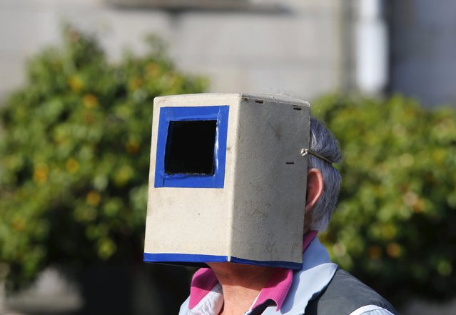 A man uses a special solar visor as he looks at a partial solar eclipse in a square of Pontevedra in the northwest Spain March 20, 2015. (Photo by Miguel Vidal/Reuters)