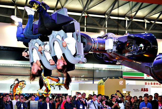 "Visitors ride in a robot arm called ""ROBOcoaster"" at the China International Industry Fair 2013 in Shanghai on November 6, 2013. Chinese manufacturing grew at its strongest pace in 18 months in October, figures showed recently, but government and independent analysts warned underlying data suggest economic weaknesses remain. (Photo by Peter Parks/AFP Photo)"