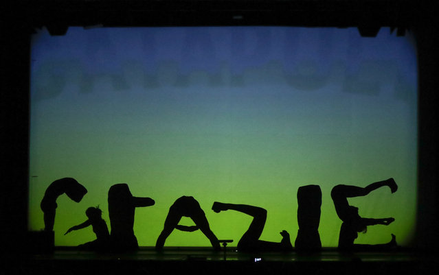 """In this photo taken on Tuesday, December 20, 2016, dancers of the U.S. company """"Catapult"""" create the Italian word """"Grazie"""" (Thank you) at the end of their show """"Magic Shadows"""", in Milan, Italy. (Photo by Luca Bruno/AP Photo)"""