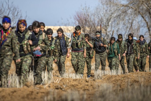 Female fighters of the Kurdish People's Protection Units (YPG) carry their weapons as they walk in the western countryside of Ras al-Ain January 25, 2015. (Photo by Rodi Said/Reuters)