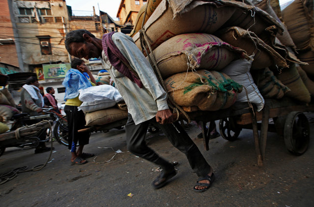 A labourer pulls a cart loaded with sacks of spices at a wholesale spice and chemical market in the old quarters of Delhi, India, December 19, 2016. Picture taken December 19, 2016. (Photo by Adnan Abidi/Reuters)