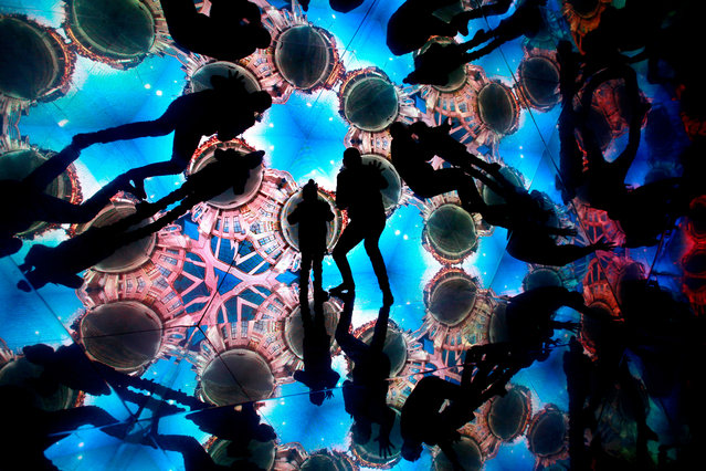 "People take part in the interactive object Kaleidoscope ""Time Machine"" during the Light Festival Staro Riga in Riga, Latvia, 17 November 2018. (Photo by Toms Kalniņš/EPA/EFE)"