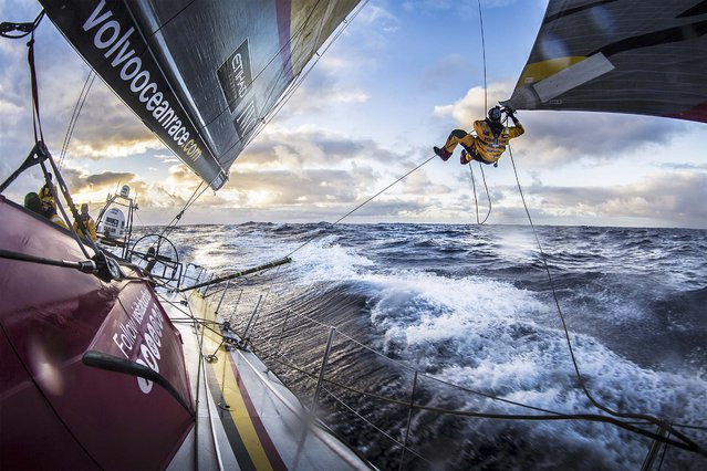 "In this handout image provided by the Volvo Ocean Race, Leg 5 to Itajai onboard Abu Dhabi Ocean Racing. Luke ""Parko"" Parkinson swings out over the southern ocean to tie a changing sheet on the FRO at sunset on March 23, 2015. (Photo by Matt Knighton/Abu Dhabi Ocean Racing/Volvo Ocean Race via Getty Images)"