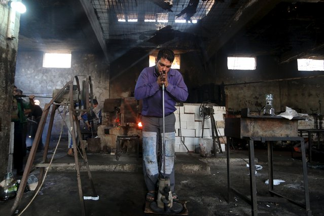 An artisan casts heated glass at a factory that recycles glass in Idlib countryside, Syria November 9, 2015. (Photo by Ammar Abdullah/Reuters)