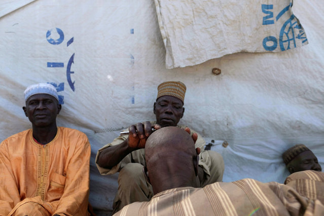 A barber shaves another man's head in a camp for internally displaced people in Bama, in Borno state, Nigeria November 23, 2017. (Photo by Paul Carsten/Reuters)