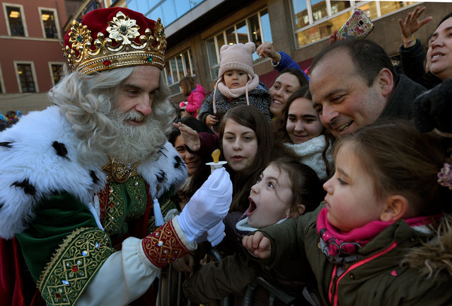 A man dressed as one of the Three Kings receives a baby pacifier from a girl during the Epiphany parade in Gijon, Spain January 5, 2017. (Photo by Eloy Alonso/Reuters)