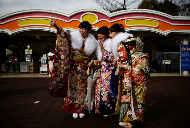 "Japanese women wearing kimonos take a ""selfie"" after their Coming of Age Day celebration ceremony at an amusement park in Tokyo, Japan January 9, 2017. (Photo by Kim Kyung-Hoon/Reuters)"