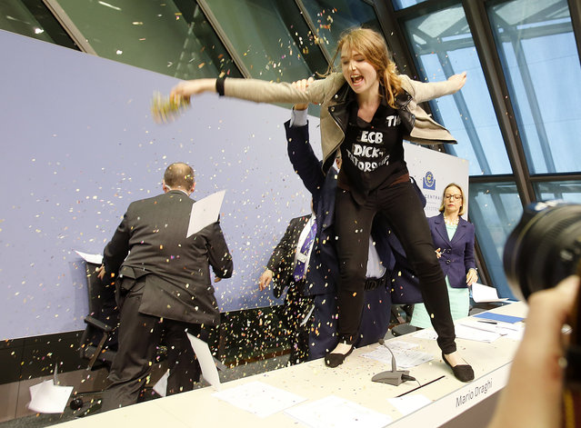 An activist stands on the table of the podium throwing paper at ECB President Mario Draghi, left covered, during a press conference of the European Central Bank in Frankfurt, Germany, Wednesday, April 15, 2015. (Photo by Michael Probst/AP Photo)