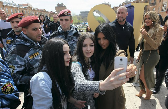 U.S. television personality Kim Kardashian (R, front) poses for a picture with local residents, with her sister Khloe Kardashian standing nearby, while sightseeing in central Yerevan, April 9, 2015. Kardashian received a rapturous welcome in her ancestors' homeland, Armenia, on a visit that could draw attention to the 100th anniversary of mass killings of Armenians in 1915. (Photo by Vahram Baghdasaryan/Reuters)