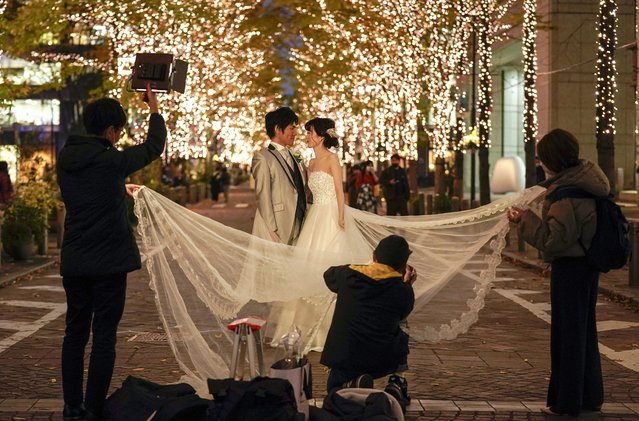 A couple poses for photos commemorating their marriage with seasonal illumination in Tokyo, Japan, 08 December 2020. A wedding information magazine explained situation of wedding ceremony in Japan in October 2020 that 90 percent of wedding ceremonies had been cancelled du to the COVID-19 Coronavirus pandemic in May 2020. It was recovered to about 64 percent of weddings scheduled for September 2020. The wedding information magazine presumes postponed weddings are expected to decrease and impact on weddings due to the coronavirus will be very limited next year. Take and Give Needs, Japan's biggest company of wedding hall management, has postponed 600 of the 1200 weddings scheduled for March 2020 to June. The number of weddings in the first half of 2020 was only 36.0 percent year-on-year due to the impact of the new coronavirus. (Photo by Kimimasa Mayama/EPA/EFE)