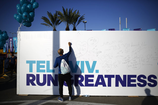 A runner writes on a billboard before participating in a marathon in Tel Aviv, Israel February 26, 2016. (Photo by Amir Cohen/Reuters)