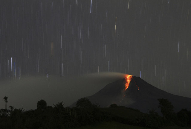 A long exposure photo shows star trails as Mount Sinabung volcano spews hot lava as seen from Jraya village in Karo district, Indonesia's North Sumatra province, January 9, 2014. About 20,000 villagers have been evacuated since authorities raised the alert status for Sinabung to the highest level in November 2013, local media reported on Monday. (Photo by Roni Bintang/Reuters)